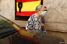 Women wearing protective face masks walk past a Spanish flag with a black ribbon for the victims of the coronavirus pandemic, in Madrid, Spain, May 22, 2020.
