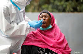 A woman reacts as a health worker takes a swab during coronavirus testing in the Kawangware neighborhood of Nairobi, Kenya, May 2, 2020.