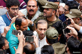 FILE - Police officers and journalists surround Mir Shakil-ur-Rahman, the owner and editor-in-chief of Geo television news channel and the Jang group of newspapers, as he leaves after court proceedings in Lahore, Pakistan, March 13, 2020.