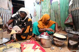 An internally displaced Somali woman and her daughter prepare their Iftar meal during the month of Ramadan at the Shabelle makeshift camp in the Hodan district of Mogadishu, Somalia, May 8, 2020.