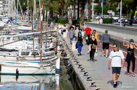People walk on the Palma de Mallorca sea promenade during hours in which individual exercise is now permitted outdoors, for the first time since Spain went on a nationwide coronavirus lockdown, in Palma de Mallorca, Spain, May 2, 2020.
