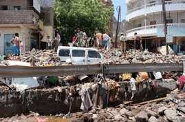 FILE - People inspect damage caused by flooding on a street in Aden, Yemen, April 22, 2020.