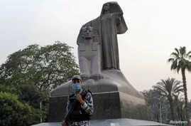 "A police officer wearing a protective face mask stands guard next to a statue called ""Egypt's Renaissance"" during Ramadan as Egypt ramps up efforts to slow the spread of the COVID-19, in Giza, May 16, 2020."