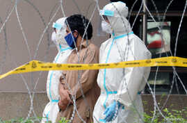 Police officers wearing protective suits pick up an illegal immigrant from an apartment under enhanced lockdown, in Kuala Lumpur, Malaysia, May 1, 2020.