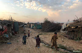 Children play outside their family's shelters at Afghan refugee camp in Islamabad, Pakistan, Feb. 13, 2020.