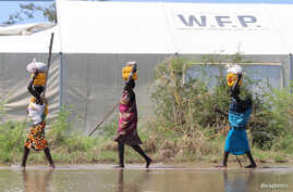 FILE- Displaced residents carry relief food as they wade through flood waters in Gumuruk, Boma state, in the Greater Upper Nile region of South Sudan, Nov. 1, 2019.