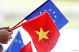 FILE- European Union and Vietnamese flags are seen at the signing ceremony of EU-Vietnam Free Trade Agreement at the government office in Hanoi, Vietnam, June 30, 2019.