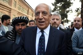 US Special Representative for Afghanistan Reconciliation Zalmay Khalilzad leaves (C) after blasts explosion were heard during…