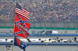 (FILES) In this file photo taken on July 10, 2015 a view of American and Confederate flags seen flying over the infield during…