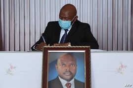 Agathon Rwasa, the head of the National Council for Freedom (CNL), Burundi's main opposition party, wears a face mask as he signs  the book of condolences at the state house in Bujumbura, June 12, 2020.