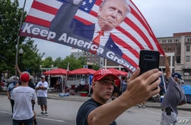 A supporter of US President Donald Trump takes a selfie near the BOK Center on June 19, 2020, in Tulsa, Oklahoma. - Trump will…