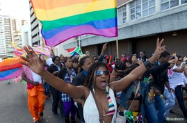 A woman holds her hands up during the Durban Pride parade where several hundred people marched through the Durban city center.