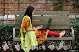 A student works on her computer sitting on a bench at Shaheed Benazir Bhutto Women's University in Peshawar, Pakistan October…