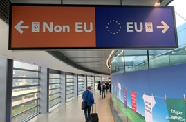 Passengers walk past a sign directing them to specific lines for EU and non EU passports as they arrive at Dublin Airport in…