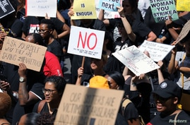 Women hold placards as they protest against gender-based violence, outside the Johannesburg Stock Exchange in Sandton,…