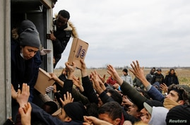 Members of United Nations High Commissioner for Refugees deliver food to migrants at Turkey's Pazarkule border crossing with…