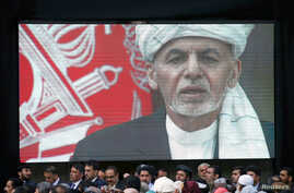 A screen shows the broadcast of Afghanistan's President Ashraf Ghani speaking during his inauguration as president, in Kabul,…