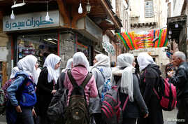School girls stand outside shops in the old city of Damascus, Syria March 12, 2020. Picture taken March 12, 2020. REUTERS/Yamam…