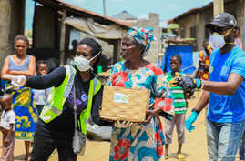 Volunteers gesture as they direct an elderly woman at an ongoing distribution of food parcels, during a lockdown by the…