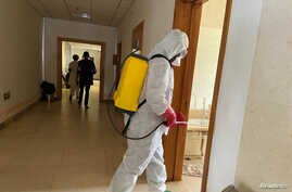 A health agent wearing protective equipment, disinfects the corridors amid the spread of the coronavirus disease (COVID-19), at…