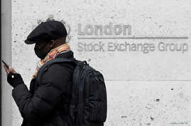 FILE PHOTO: A man wearing a protective face mask walks past the London Stock Exchange Group building in the City of London…