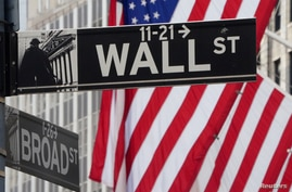 FILE PHOTO: The Wall Street sign is pictured at the New York Stock exchange (NYSE) in the Manhattan borough of New York City,…