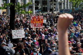 A protesters raises their fists as thousands gather outside City Hall against the death in Minneapolis police custody of George…