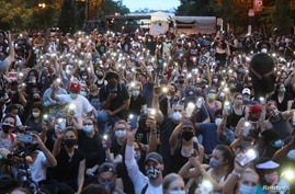 Demonstrators use the light of their cellphones as they gather during a protest against death in Minneapolis police custody