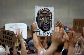 People hold up a likeness of George Floyd at a public memorial after the death in Minneapolis police custody of George Floyd in…