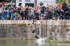 The statue of 17th century slave trader Edward Colston falls into the water after protesters pulled it down and pushed into the…