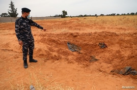 A member of security forces loyal to Libya's internationally recognized government points to a mass grave, according to Libya's Internationally recognized government officials, in Tarhouna city, Libya, June 11, 2020.