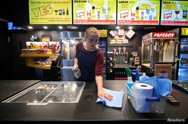 A worker disinfects high-touch areas for the reopening of a cinema following the easing of the coronavirus disease (COVID-19)…