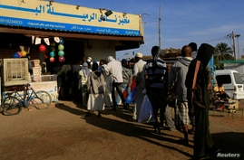 FILE PHOTO: Customers queue to buy bread at a bakery in Khartoum, Sudan,February 19, 2020. REUTERS/Mohamed Nureldin Abdallah…