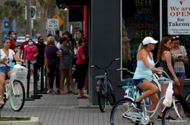 FILE - People stand in line at a Duval County restaurant by the beach after it was opened amid coronavirus disease.