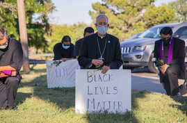 In this June 1, 2020, photo provided by the Catholic Diocese of El Paso, Bishop Mark Seitz, center, kneels