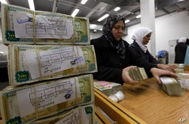 FILE - In this January 13, 2010 file photo, Syrian employees stack packets of Syrian currency in the Central Syrian Bank