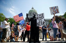 FILE - In this Friday, May 15, 2020 file photo, protesters hold a rally against Pennsylvania's coronavirus stay-at-home order…
