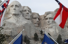 FILE - Flags frame the presidents on the Mount Rushmore monument near Keystone, South Dakota.