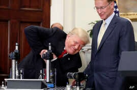 President Donald Trump attempts to crush a Corning Valor glass protective vial with Wendell P. Weeks, right, chairman and chief…