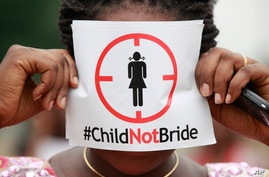FILE- In this Saturday, July 20, 2013, file photo, a woman protests against underage marriage in Lagos, Nigeria. Child marriage…