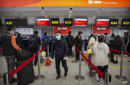 FILE- Travelers wearing face masks wait in line at the Hainan Airlines check-in counters at Beijing Capital International Airport in Beijing, March 6, 2020.