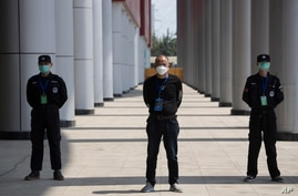 Security guards stand on duty at one of the temporary coronavirus hospitals during a visit by journalists in Wuhan, central…