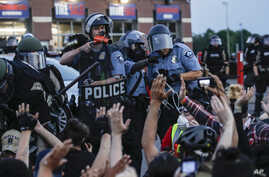 A police officer points a hand cannon at protesters who have been detained pending arrest on South Washington Street.