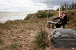 World War II D-Day veteran and Penobscot Elder from Maine, Charles Norman Shay sits on a bench next to his memorial stone at Omaha Beach prior to a ceremony in Saint-Laurent-sur-Mer, Normandy, France, Friday June 5, 2020.
