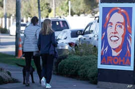 Pedestrians walk past a billboard featuring Prime Minister Jacinda Ardern with the word Aroha, meaning love, in Christchurch,…