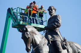 An inspection crew from the Virginia Department of General Services takes measurements as they inspect the statue of…