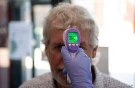 In this Tuesday, June 9, 2020 photo, a patient has his temperature taken with a non-contact infrared thermometer on arrival at…