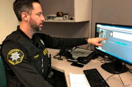 FILE - Washington County Sheriff's Office Deputy Jeff Talbot demonstrates how his agency used facial recognition software to help solve a crime, at their headquarters in Hillsboro, Oregon, Feb. 22, 2019.