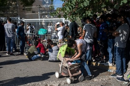 Migrants wait outside the government's Asylum Service to submit and provide documents for asylum claims, in Athens, June 11, 2020.