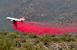 Heat ripples distort an air tanker as it drops retardant on the Bighorn Fire along the western side of the Santa Catalina…